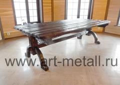 Большой деревянный стол с коваными элементами.