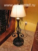 Кованая настольная лампа на деревянном основании.
