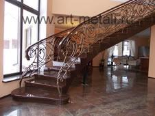 Полукруглая лестница с кованым ограждением.
