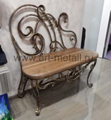 Wrought iron bench with a back.