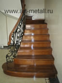 Stairs. Red wood. Wrought iron railings.