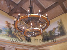 Forged chandelier stylized as a cart wheel.