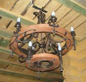 Wrought iron chandelier, stylized wagon wheel.